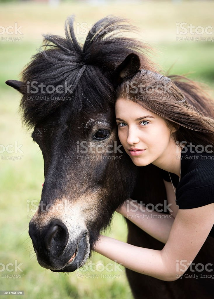 Young attractive woman touching her islandic pony stock photo