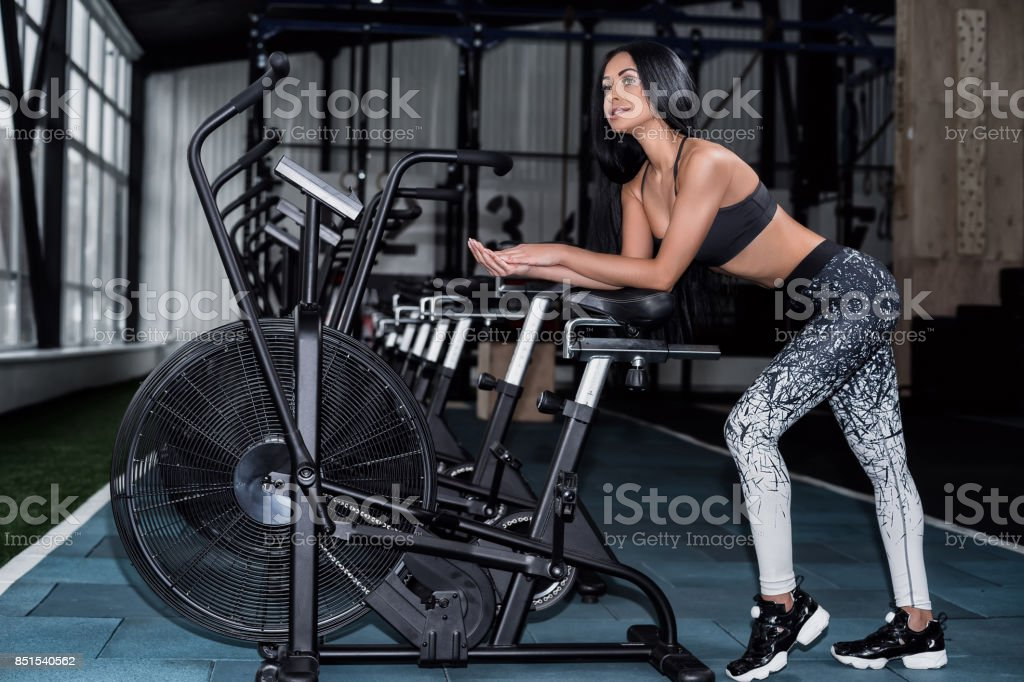 Young, attractive woman using exercise bike at the gym. Fitness female using air bike for cardio workout at crossfit gym. stock photo