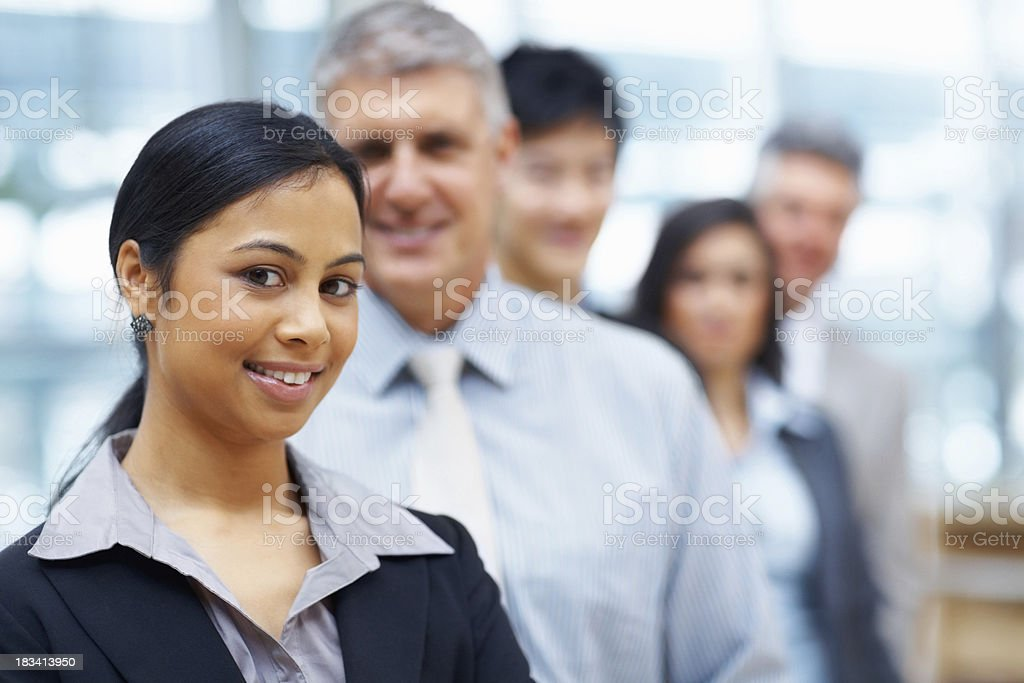 Young attractive woman with team in background royalty-free stock photo