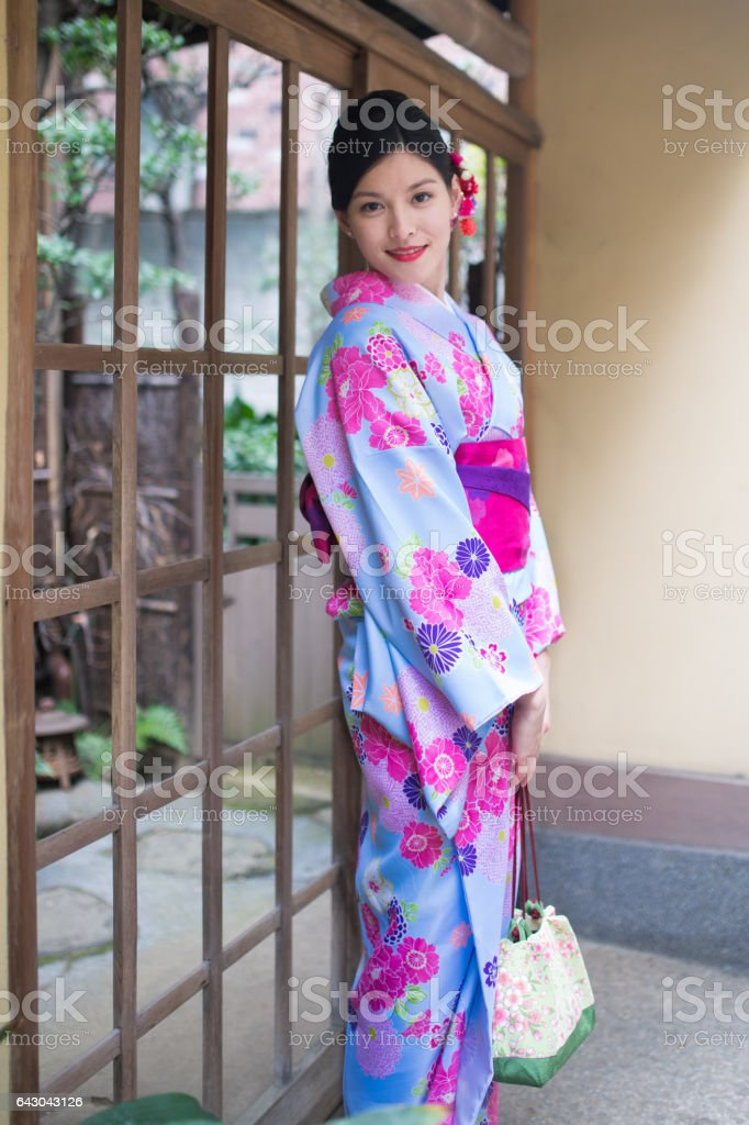 Young Austrian woman  in Kimono standing at Japanese house entrance stock photo