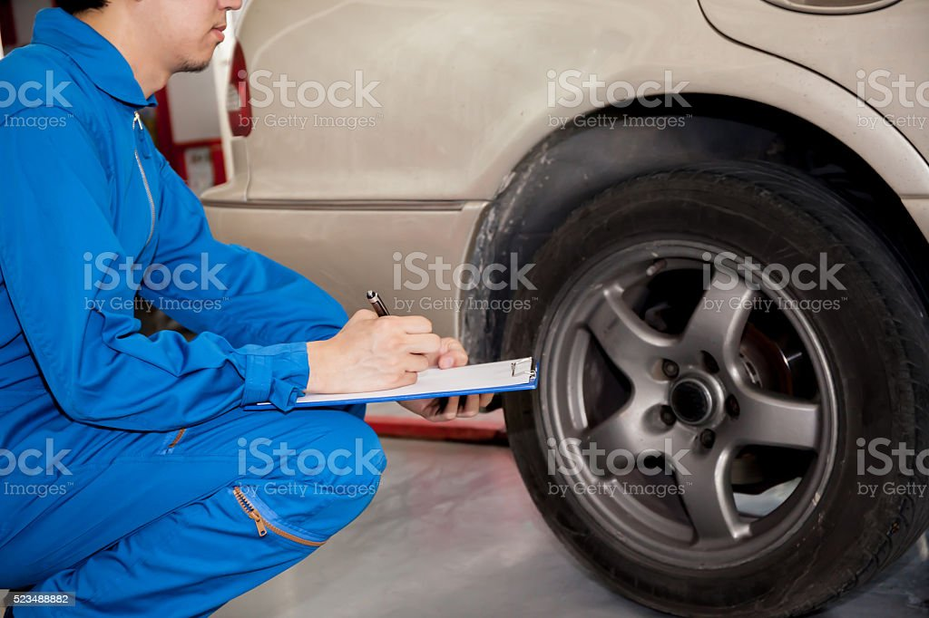 Young automotive technician checking on car tires in garage stock photo