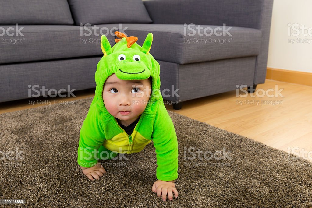 Young baby boy dressed in dinosaur stock photo