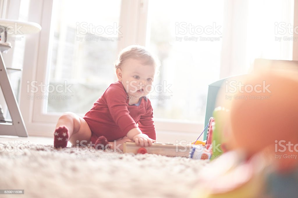 Young baby boy playing with his toys stock photo