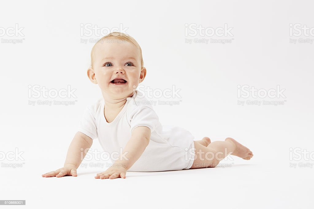 Young baby girl crawling on front, studio stock photo