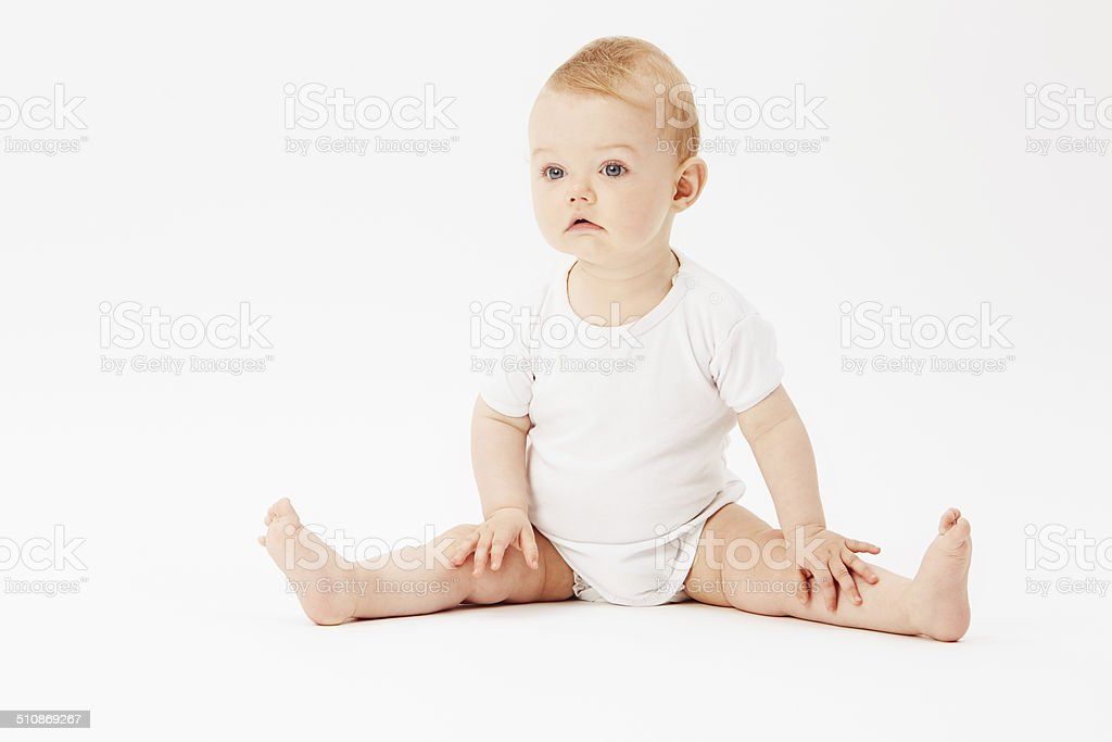 Young baby girl looking away, studio stock photo