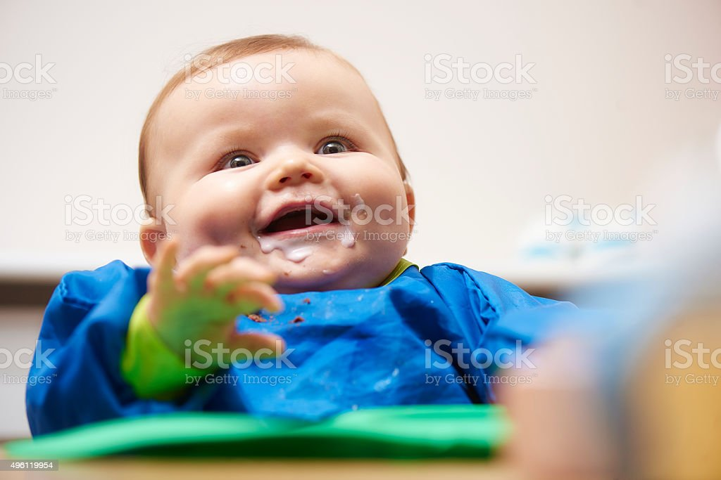Young baby laughing with yoghurt all over his face stock photo
