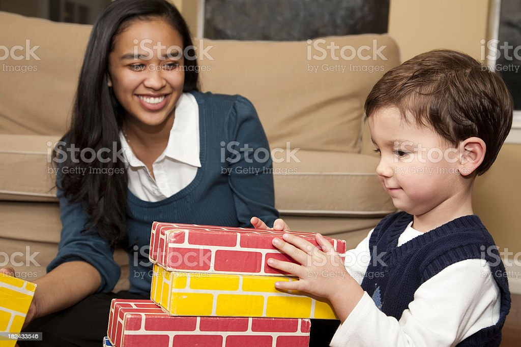 Young Baby Sitter Playing Blocks with Toddler Boy stock photo