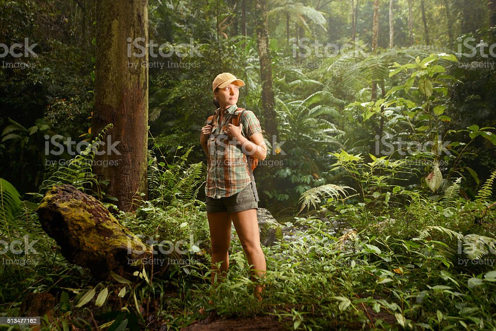 Young backpacker traveling along rain forest. stock photo
