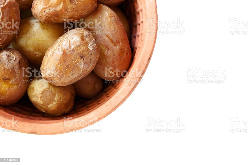 Young baked potatoes in clay pot on white stock photo