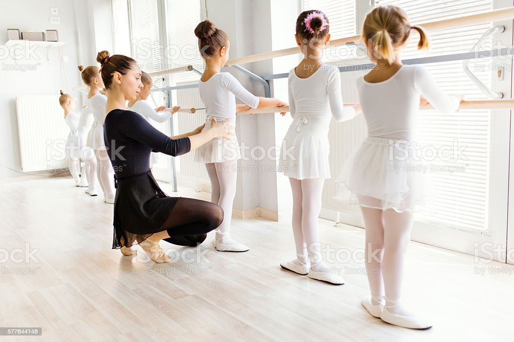 Young ballerina assisting little girls on a ballet class. stock photo