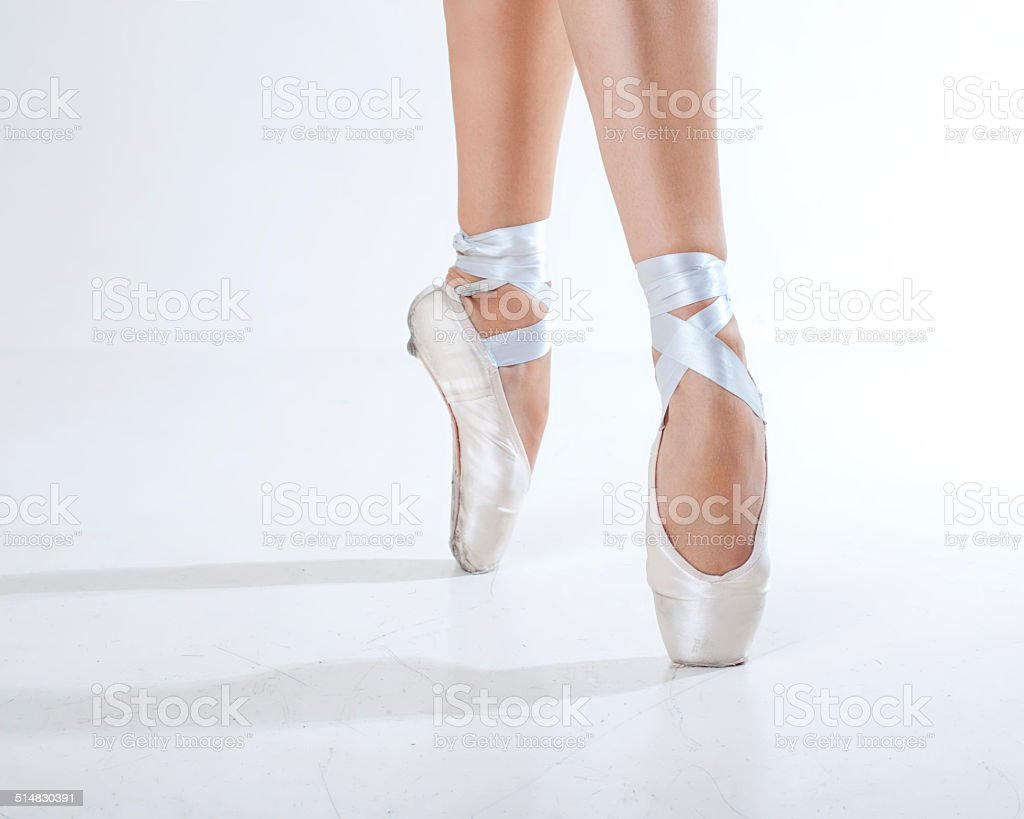 Young ballerina dancing, closeup on legs and shoes stock photo