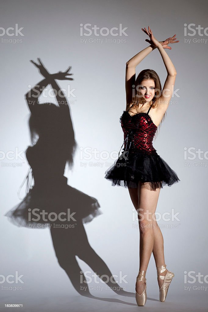 Young ballerina dancing on gray background royalty-free stock photo