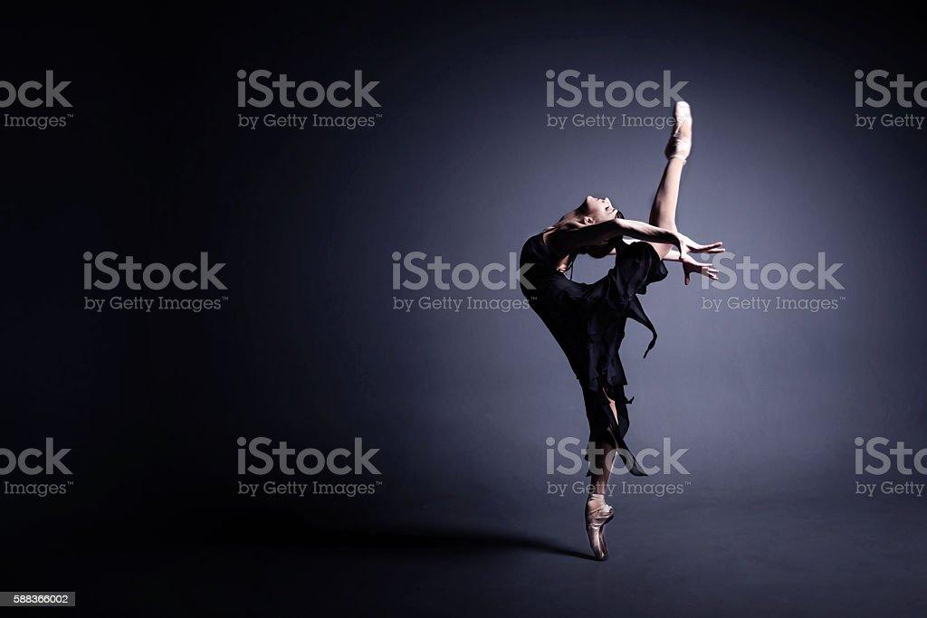 Young ballerina in a black suit is dancing in dark stock photo