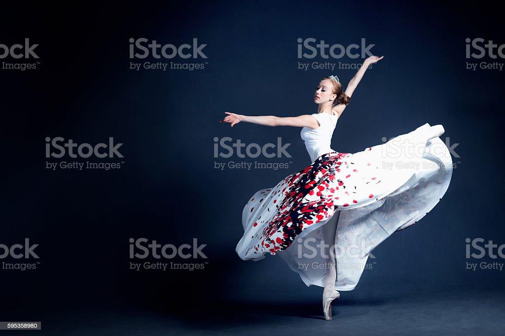 Young ballerina is dancing in a dark photostudio stock photo