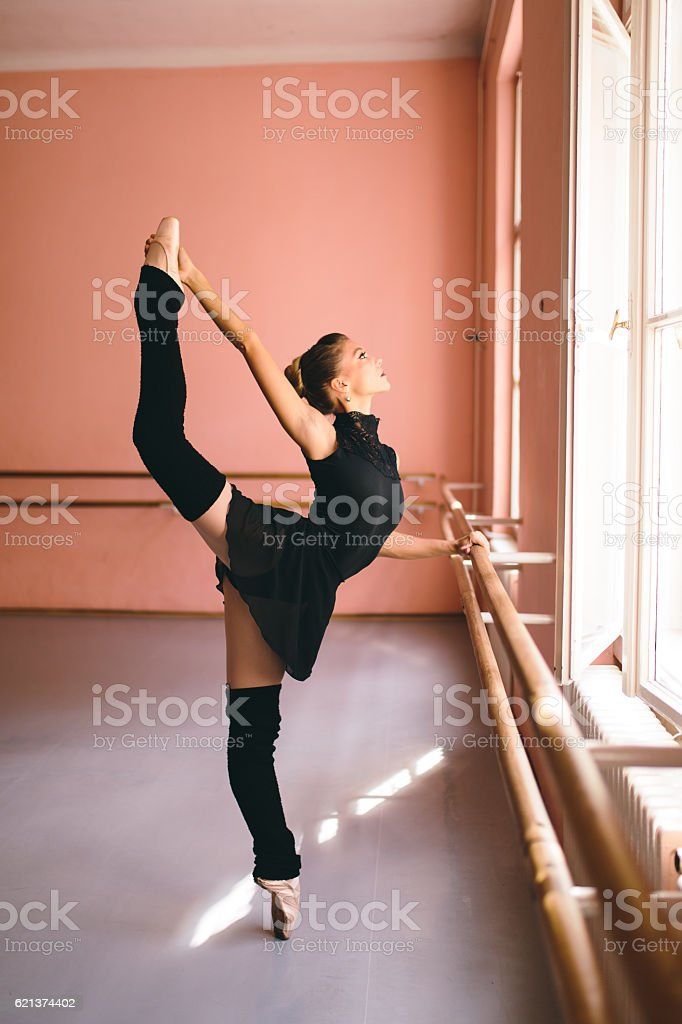 Young ballerina tip toeing next to a barre stock photo
