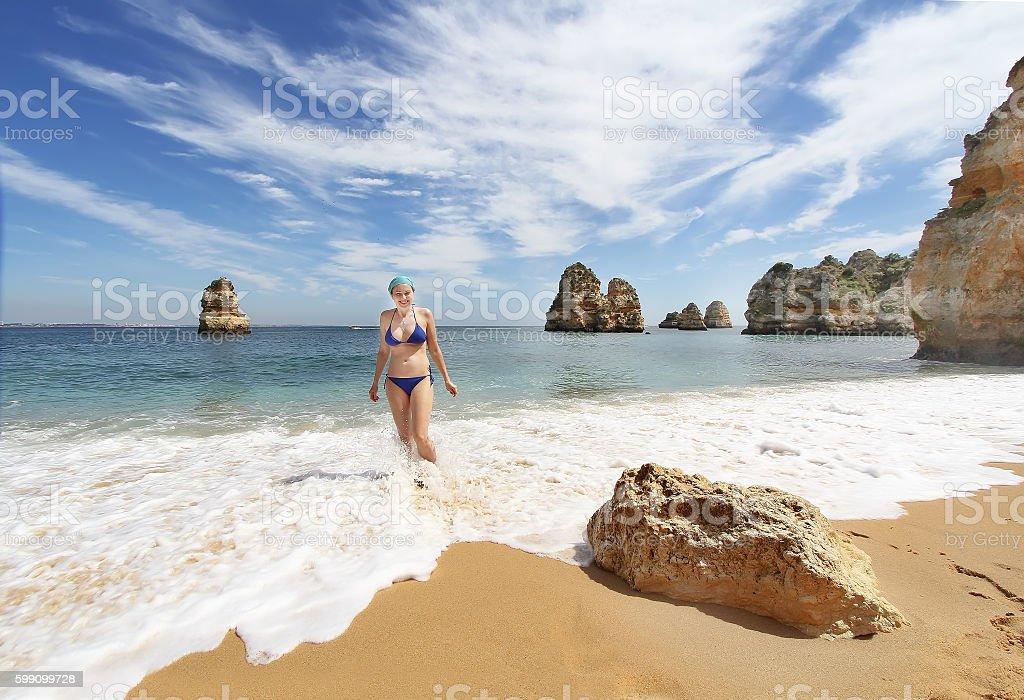 Young barefoot woman in bikini  on the Rocky beach stock photo