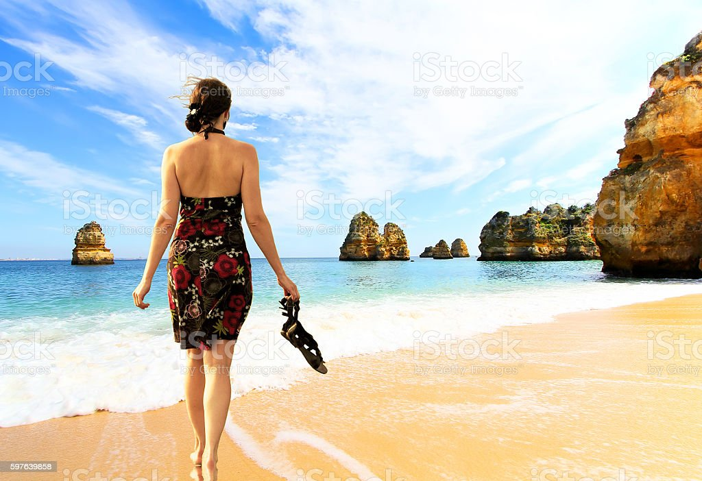 Young barefoot woman in dress  on the Rocky beach stock photo
