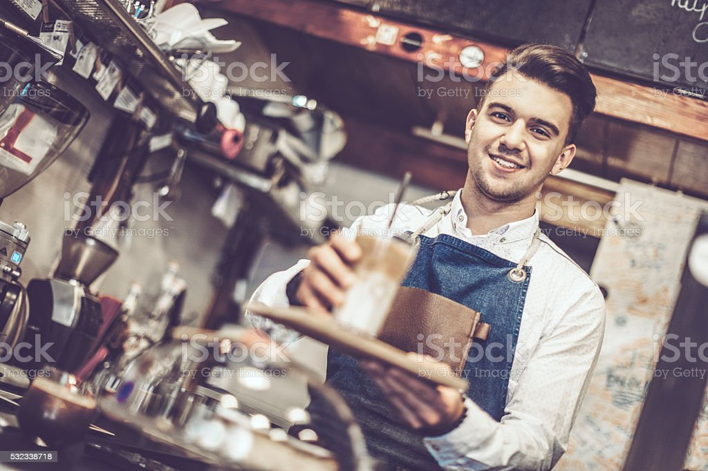 Young barista is offering a coffee speciality stock photo