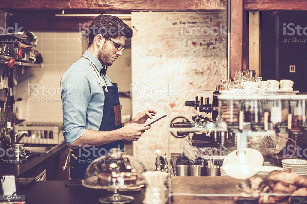 Young barista is using a digital tablet stock photo