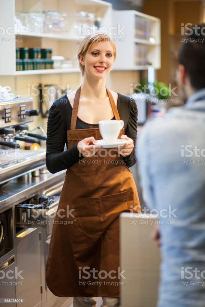 Young barista serving coffee stock photo