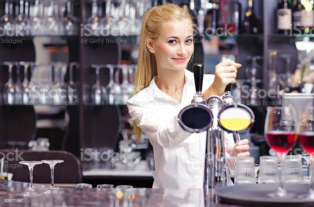 Young barmaid pulling pints stock photo