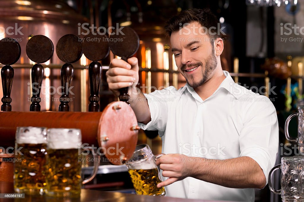A young bartender filling a mug with freshly tapped beer stock photo