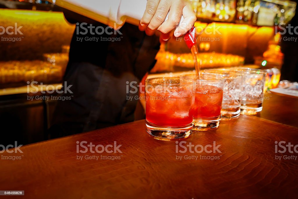 Young bartender pouring juice stock photo
