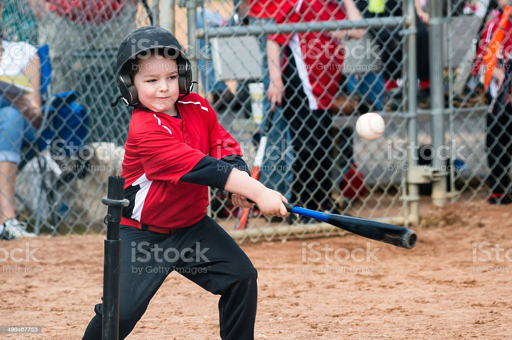 Young baseball player hitting ball off a tee stock photo