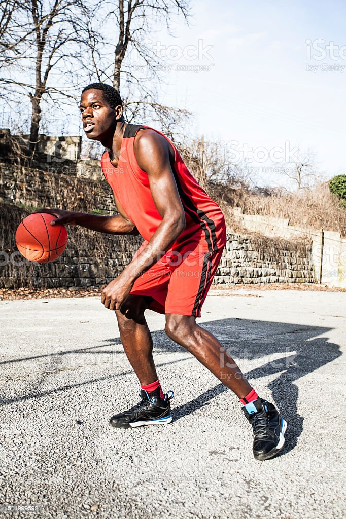 Young basketball player dribbling stock photo