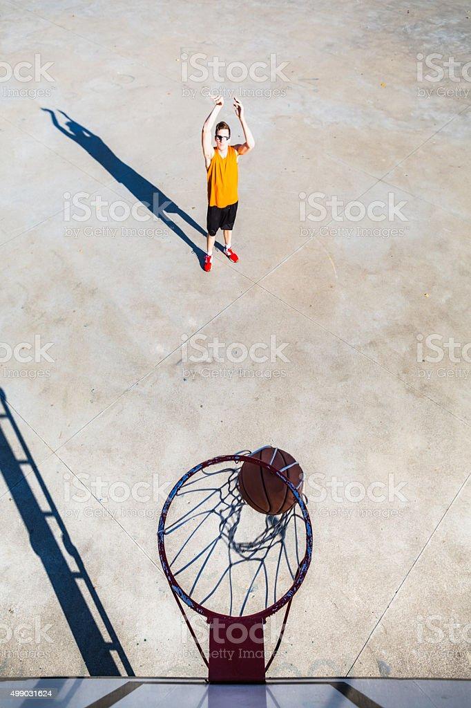 Young basketball player throwing ball into hoop stock photo