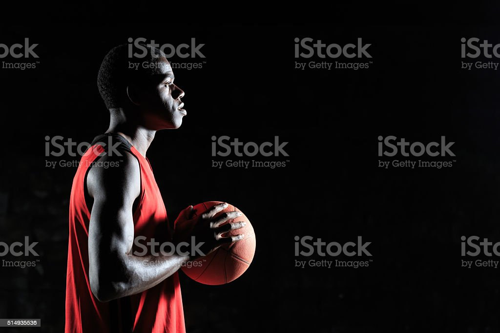 Young basketball player with a ball - side view stock photo