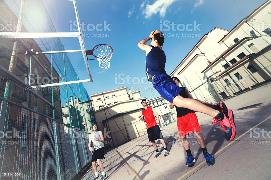 young basketball players playing with energy in a urban place stock photo