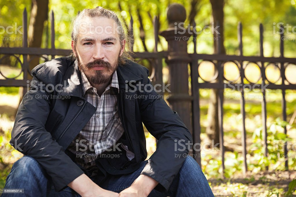 Young bearded Asian man sitting in summer park stock photo