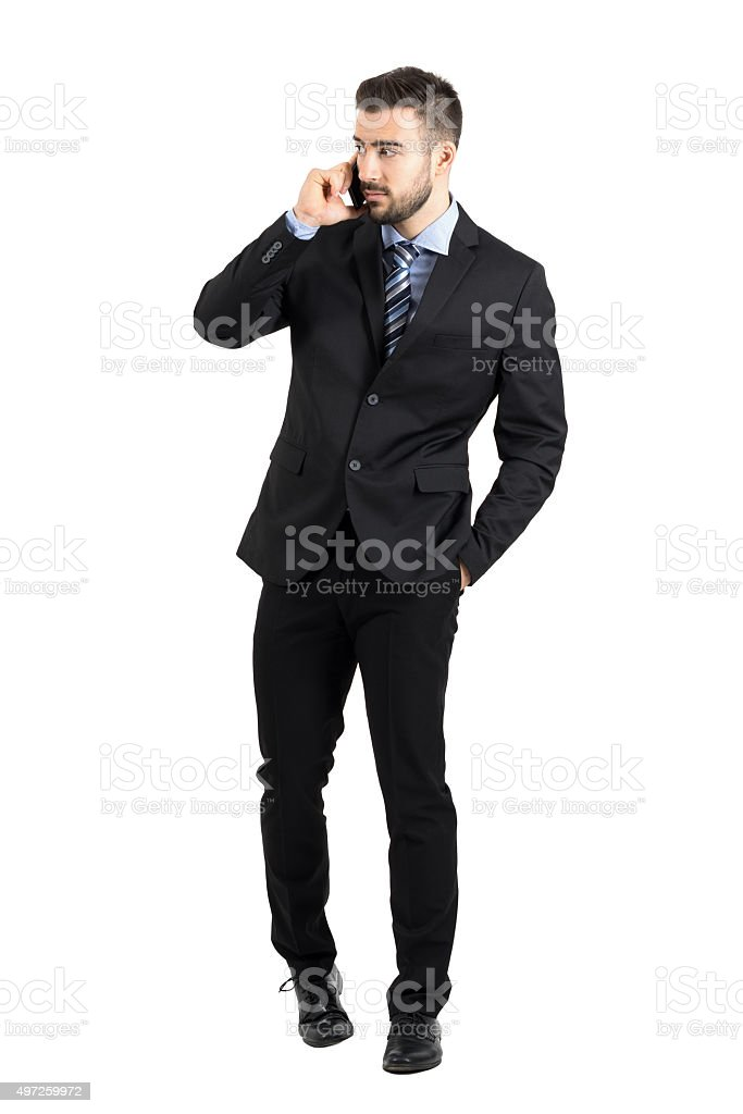 Young bearded businessman talking on the phone looking away stock photo