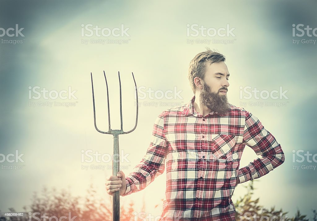 young bearded farmer in red checkered shirt with old pitchfork stock photo