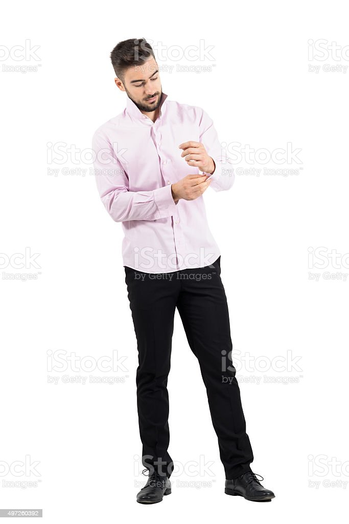 Young bearded groom getting dressed for wedding stock photo