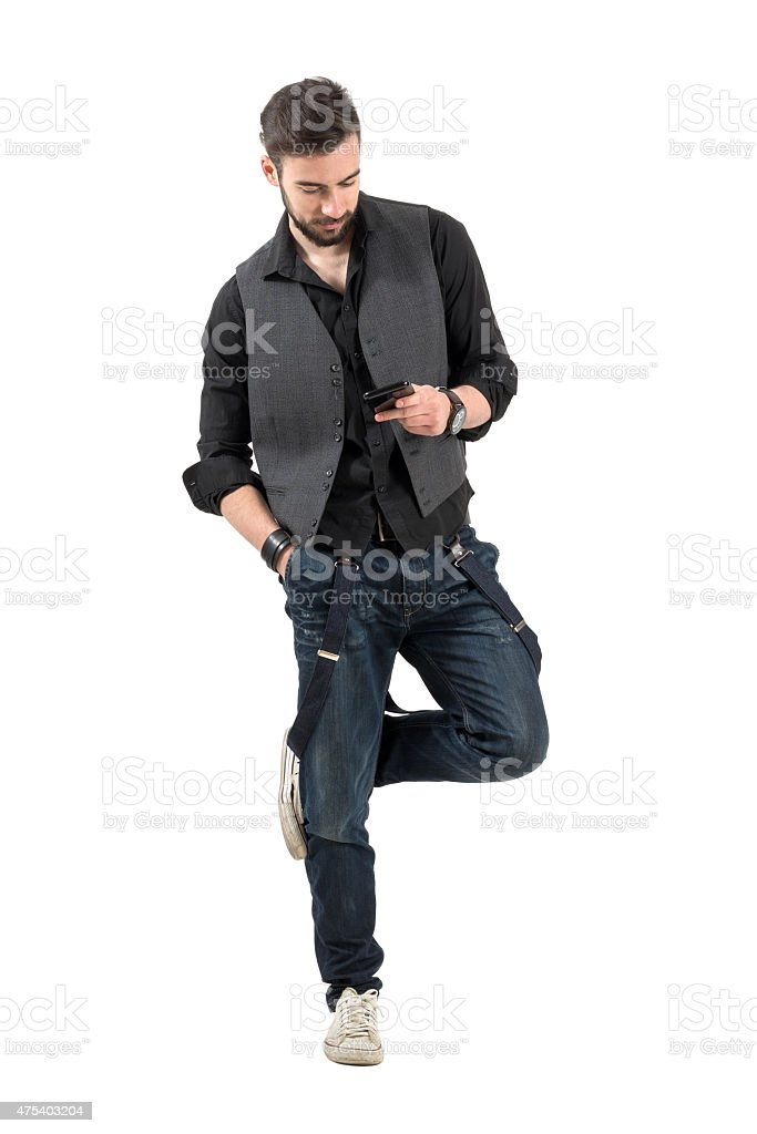 Young bearded guy scratching rubbing legs while on smartphone stock photo