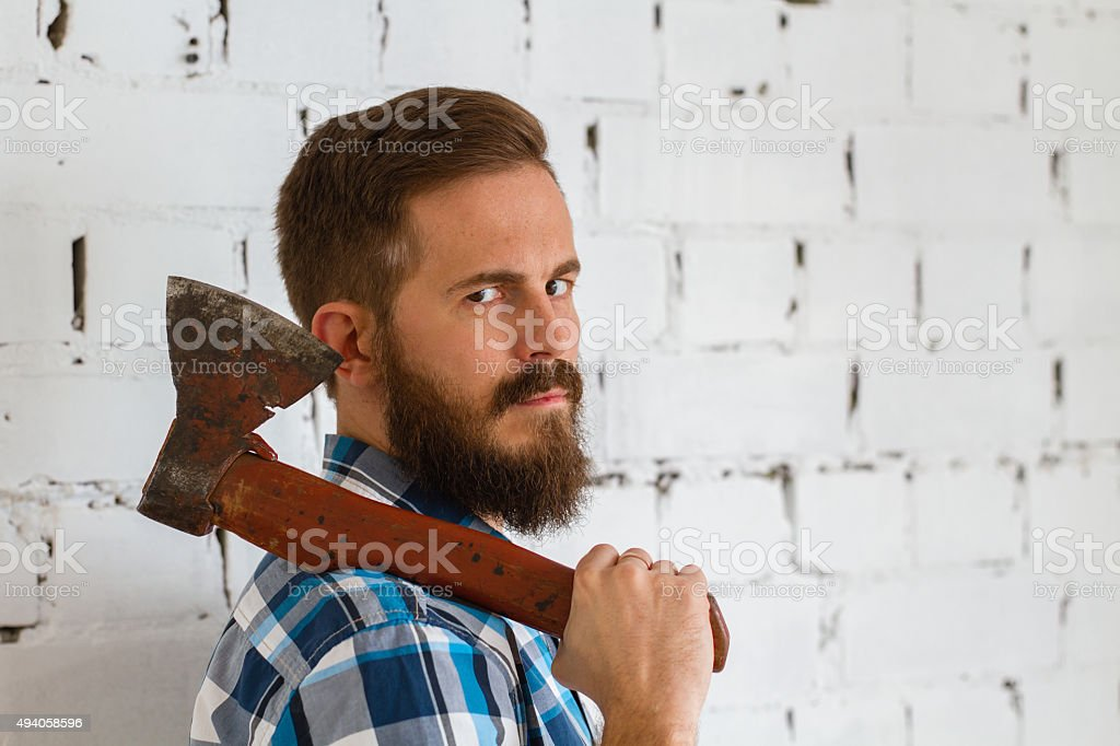 Young bearded lumberjack with red axe stock photo