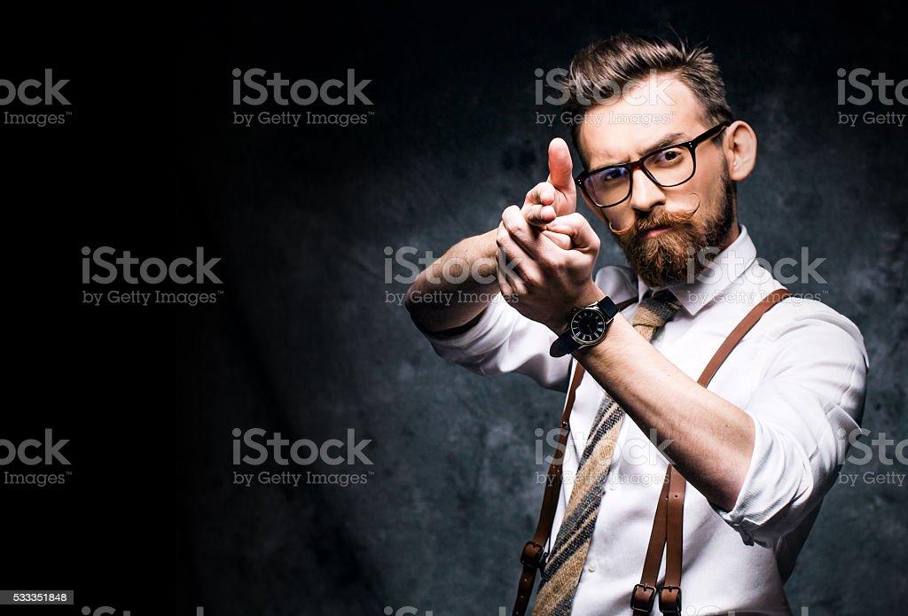 Young bearded man aiming a finger gun stock photo