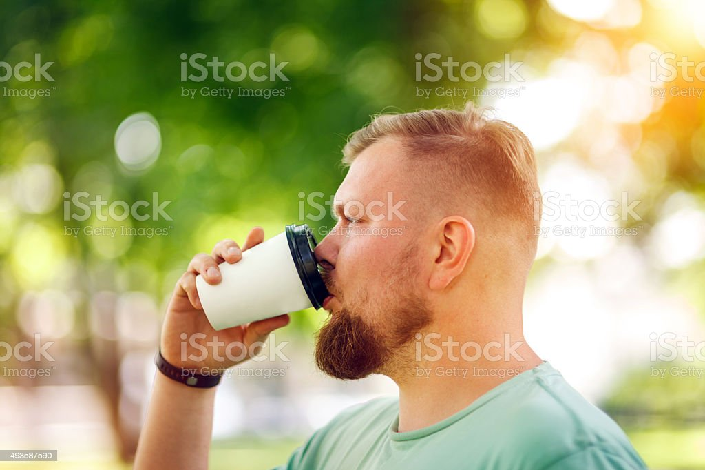 Young bearded man drinking coffee stock photo
