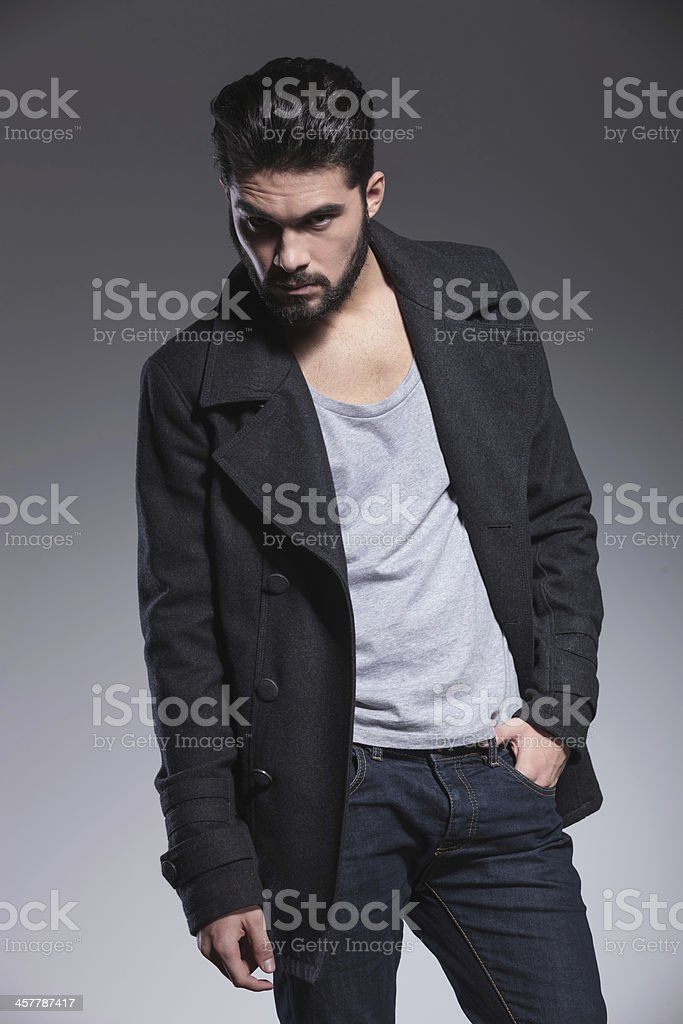 young bearded man in long coat is posing royalty-free stock photo