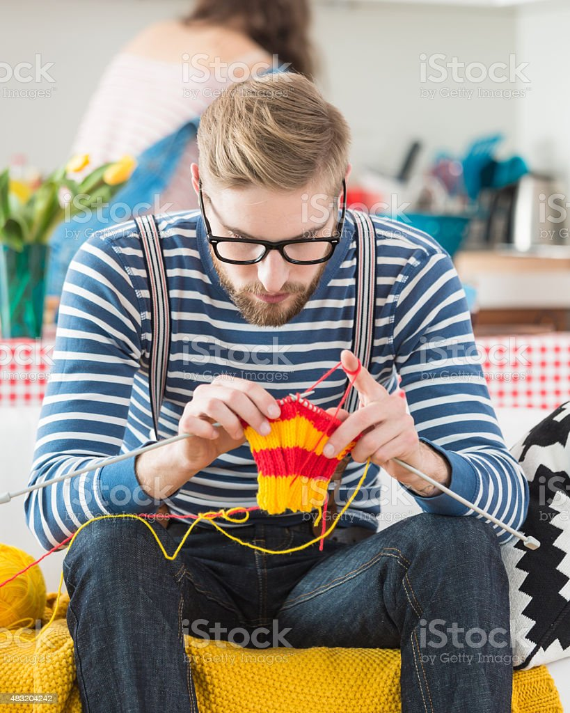 Young bearded man knitting stock photo