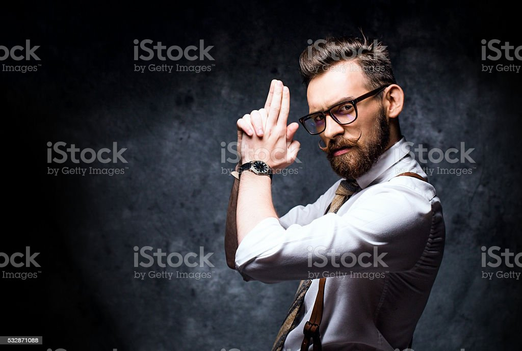 Young bearded man posing with a finger gun stock photo