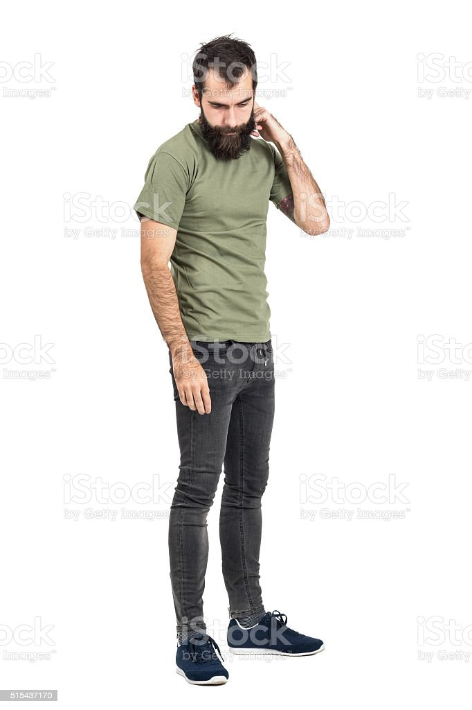 Young bearded man scratching head looking down side view stock photo