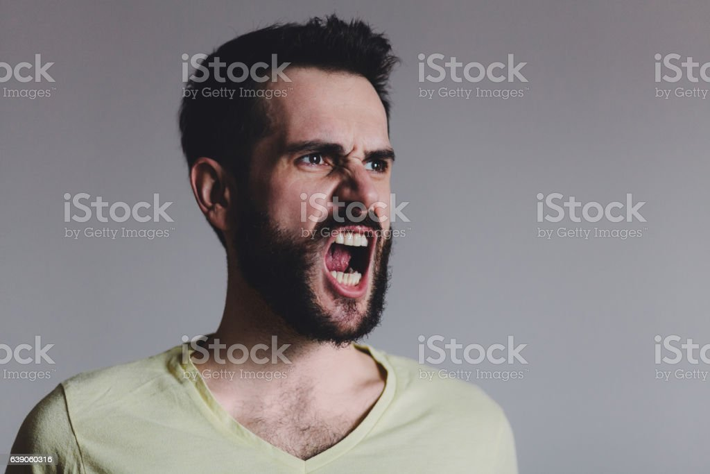 Young bearded man showing negative emotion stock photo