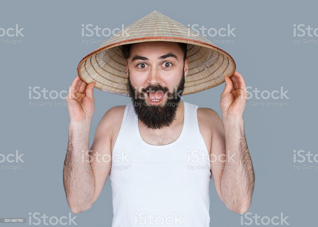 Young bearded man surprised in chinese hat stock photo