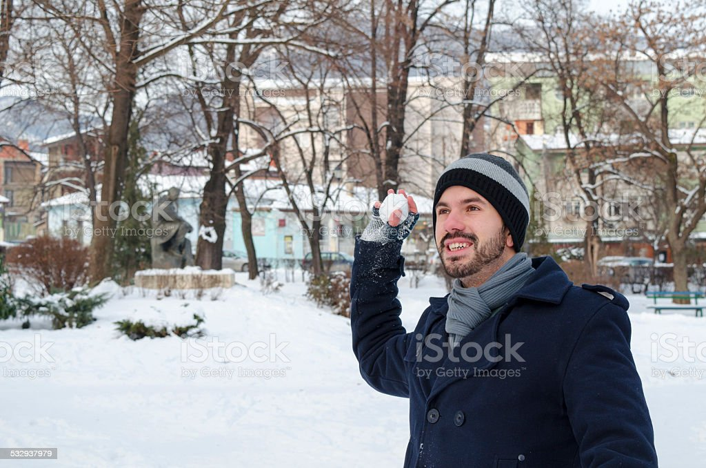 Young bearded man throwing a snowball royalty-free stock photo