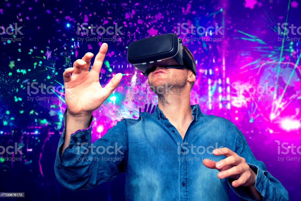 Young bearded man wearing virtual reality glasses in modern interior design coworking studio. Smartphone using with VR goggles headset. Horizontal,flares effect, blurred background stock photo
