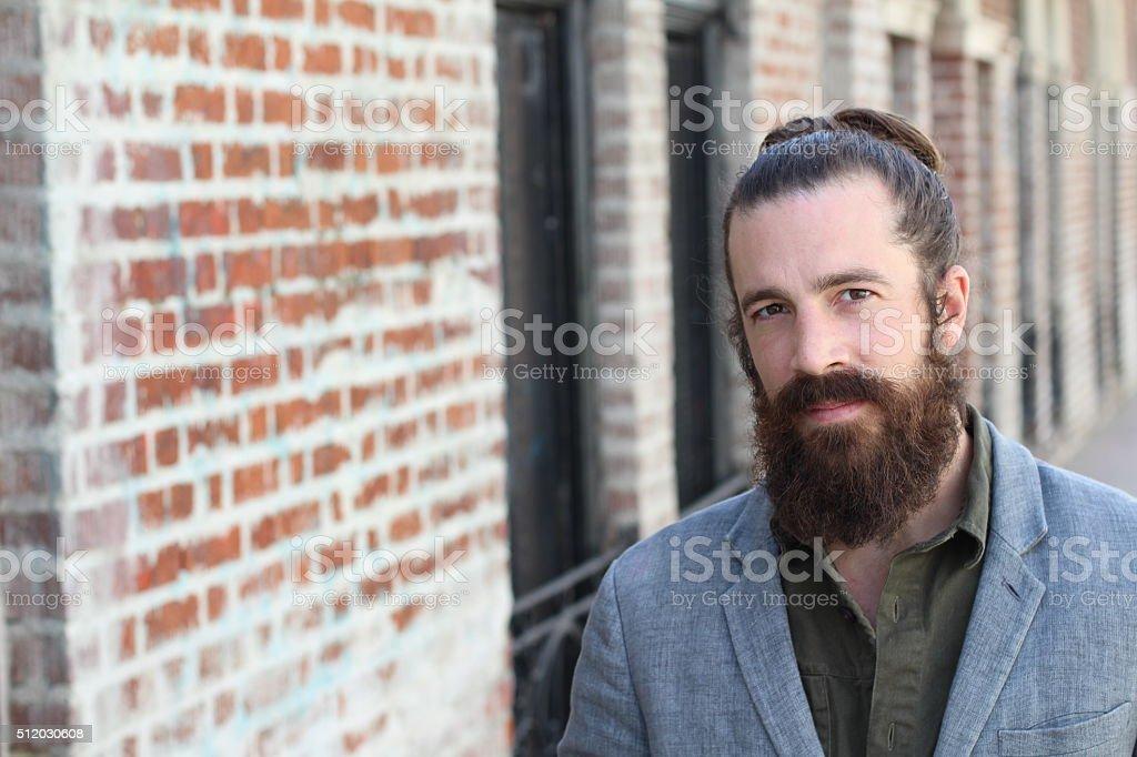young bearded man with man bun stock photo