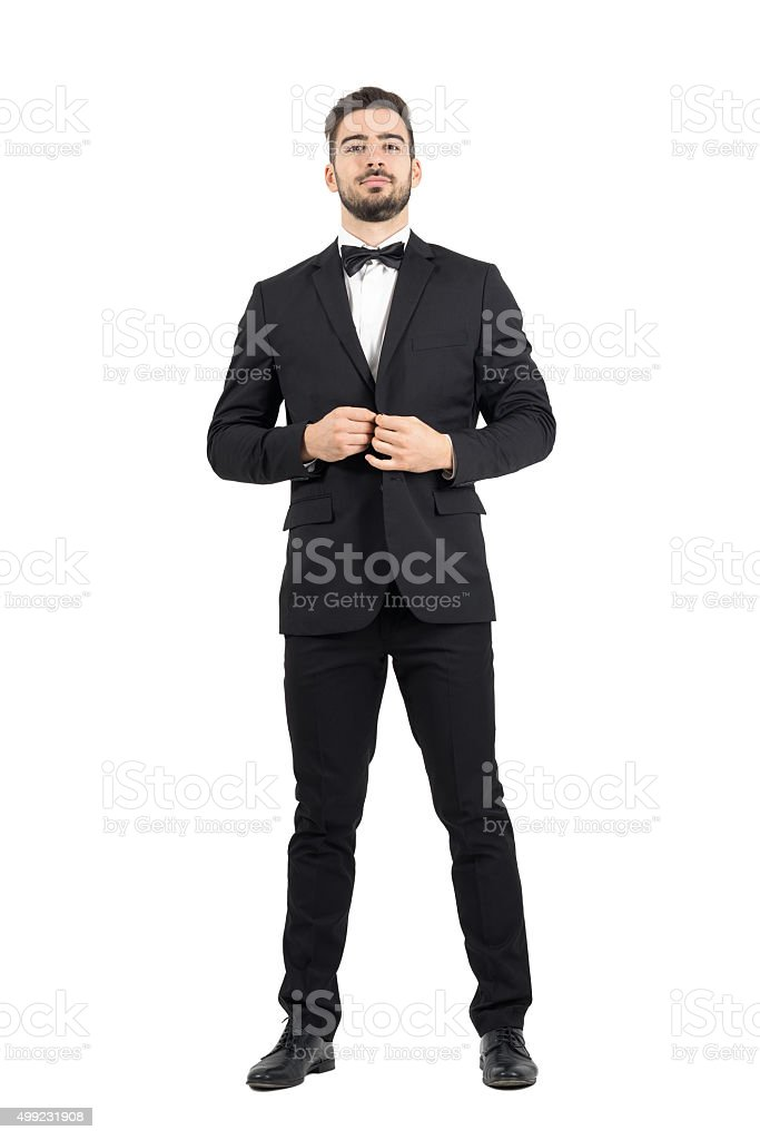Young bearded wealthy man buttoning tuxedo with bow tie stock photo